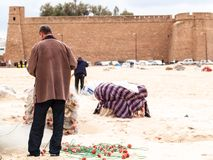 La Tunisia al pescatore di Hammamet prepara le reti da pesca sulla spiaggia Fotografia Stock Libera da Diritti