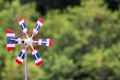 La turbine de vent thaïlandaise de drapeau, fond brouillé de forêt naturelle, le vent souffle, entraînant le propulseur tourner,  photos libres de droits