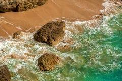 La turquoise/bleu ondule sur une plage sablonneuse avec des roches Photo stock