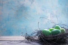 La turquoise a coloré l'eggsin de Pâques un nid sur les planches en bois rustiques a Photos stock