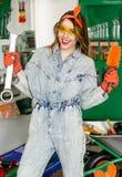 La tuta ed i vetri d'uso del denim della giovane donna con la tenuta lunga dei capelli in mani strappano e spazzolano e sorridere Fotografie Stock