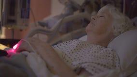 La TV clignote dans la chambre d'hôpital sombre tandis que des montres de patient banque de vidéos