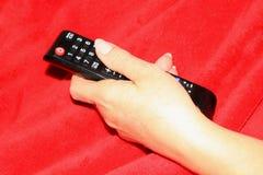 La TV del control de la mujer teledirigida foto de archivo