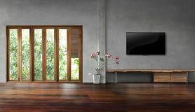 La TV en el muro de cemento con las ventanas altas en pisos de madera viejos vacia la sala de estar foto de archivo