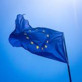 La UE desigual retroiluminada señala por medio de una bandera Imagen de archivo
