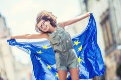 La UE señala por medio de una bandera Muchacha feliz linda con la bandera de la unión europea Adolescente joven que agita con la  Foto de archivo libre de regalías