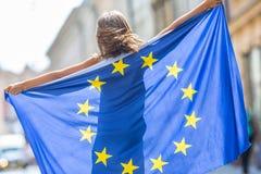 La UE señala por medio de una bandera Muchacha feliz linda con la bandera de la unión europea Yo Imagenes de archivo