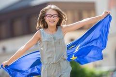 La UE señala por medio de una bandera Muchacha feliz linda con la bandera de la unión europea Yo Imágenes de archivo libres de regalías