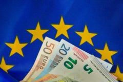 La UE señala por medio de una bandera y los billetes de banco euro Imagen de archivo libre de regalías