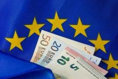 La UE señala por medio de una bandera y las notas euro Imagen de archivo libre de regalías