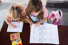 La una opinión superior adorable de las ilustraciones del dibujo de la niña sobre los creyones en un cuaderno y la muchacha apren fotos de archivo