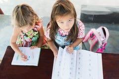 La una opinión superior adorable de las ilustraciones del dibujo de la niña sobre los creyones en un cuaderno y la muchacha apren imagen de archivo