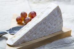 La una pieza del brie franc?s del queso suave con el molde blanco y el olor fuerte, sirvi? con las uvas frescas fotos de archivo libres de regalías