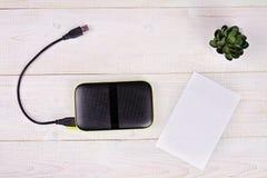 La unidad de disco duro externa portátil con el cable del USB y el documento en blanco del mensaje sobre el fondo de madera blanc Foto de archivo libre de regalías