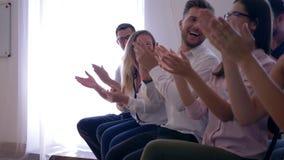 La unidad de negocio alegre aplaude el altavoz después de la presentación en el primer del seminario de entrenamiento almacen de video