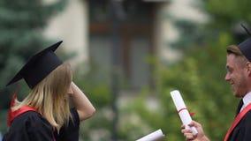 La universidad gradúa jugando la lucha con los diplomas, competencia para el empleo almacen de metraje de vídeo