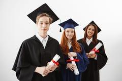 La universidad internacional feliz tres gradúa el júbilo sonriente que sostiene los diplomas sobre el fondo blanco Abogados futur Imagen de archivo