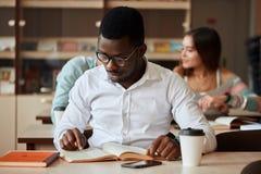 La universidad masculina afroamericana studen la preparación para los exámenes en la biblioteca imagen de archivo libre de regalías