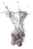 La uva azul cayó en el agua con el chapoteo Fotografía de archivo