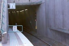 La vía de ferrocarril vacía del túnel del subterráneo escénica con el tren vacío sigue la abertura de la cueva en la montaña y el imágenes de archivo libres de regalías