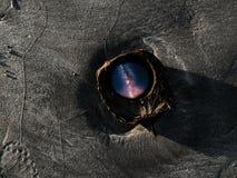 La vía láctea corrige en una cáscara del coco en una playa arenosa foto de archivo