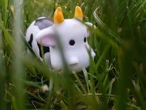 La vaca del juguete está comiendo la hierba Foto de archivo