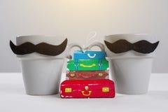 La vacanza, viaggia 2 amici maschii Uomo-uomo simbolico delle tazze, un mazzo di valigie di viaggio Immagini Stock