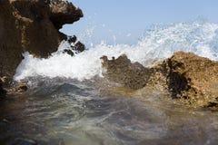 La vague de mer éclaboussant au-dessus du rivage bascule avec un pulvérisateur de haute mer Photo stock