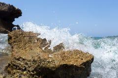 La vague de mer éclaboussant au-dessus du rivage bascule avec un pulvérisateur de haute mer Photos libres de droits