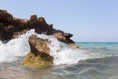 La vague de mer éclaboussant au-dessus du rivage bascule avec un pulvérisateur de haute mer Images libres de droits