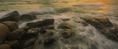La vague se brise vers le bas sur les roches Image stock