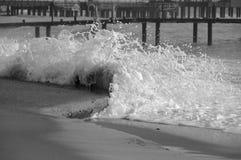 La vague se casse contre le rivage pour de petites baisses et mousse Image stock