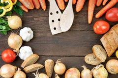 La vaisselle de cuisine en bois avec des légumes se mélangent et panent sur la table Photographie stock