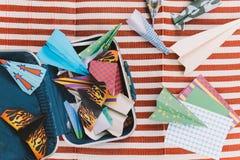 La valigia aperta con gli aerei della carta di colore sul bianco e sul rosso barra la stuoia Immagine Stock Libera da Diritti