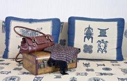 La valigia, la borsa e la sciarpa sono sul sofà. Immagini Stock