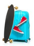 La valise bleue, espadrilles, planche à roulettes sur le fond blanc Photographie stock