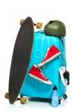 La valise bleue, espadrilles, planche à roulettes sur le fond blanc Photos stock