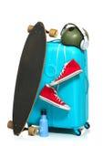 La valise bleue, espadrilles, planche à roulettes sur le fond blanc Photos libres de droits