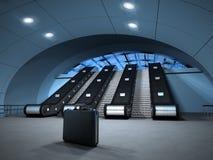 La valise est partie au bas d'un escalator Image libre de droits