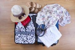 La valise ouverte avec la femelle occasionnelle vêtx le chapeau, lunettes de soleil, la robe, chaussures, sur la fin en bois de v Photo stock