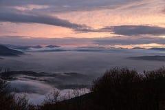 La vallée de l'Ombrie en hiver a rempli par la brume au coucher du soleil, d'émergence Photographie stock