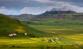 La vallée entre les montagnes avec des maisons et les champs, Islande Photographie stock libre de droits