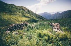 La vallée verte de montagnes avec les pierres antiques clôturent Landscape Images libres de droits