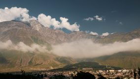 La valle pittoresca con le case di Stepantsminda Kazbegi con le alte montagne sui precedenti, Georgia Immagini Stock Libere da Diritti