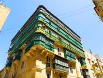 La Valletta building, Malta, green balconies. Corner building with green balconies in La Valletta, Malta, in a sunny day Stock Images
