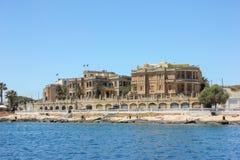 La Valletta, Malta - maggio 2018: Vecchie costruzioni in grande porto Turisti che si rilassano sulla spiaggia rocciosa immagini stock