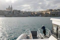 View of Valletta, the capital city of Malta. La Valletta, Malta - 31 October 2017: man on the ferry leading to La Valletta on Malta Royalty Free Stock Photo
