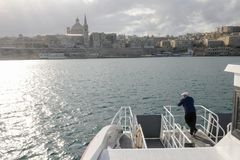 View of Valletta, the capital city of Malta. La Valletta, Malta - 31 October 2017: man on the ferry leading to La Valletta on Malta Stock Photo