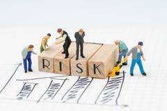 La valutazione del rischio per l'affare o l'investimento, la figura miniatura uomo d'affari e la condizione del gruppo della soci immagini stock