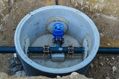La valve d'approvisionnement en eau est située dans le puits et est peinte bleue Photos libres de droits